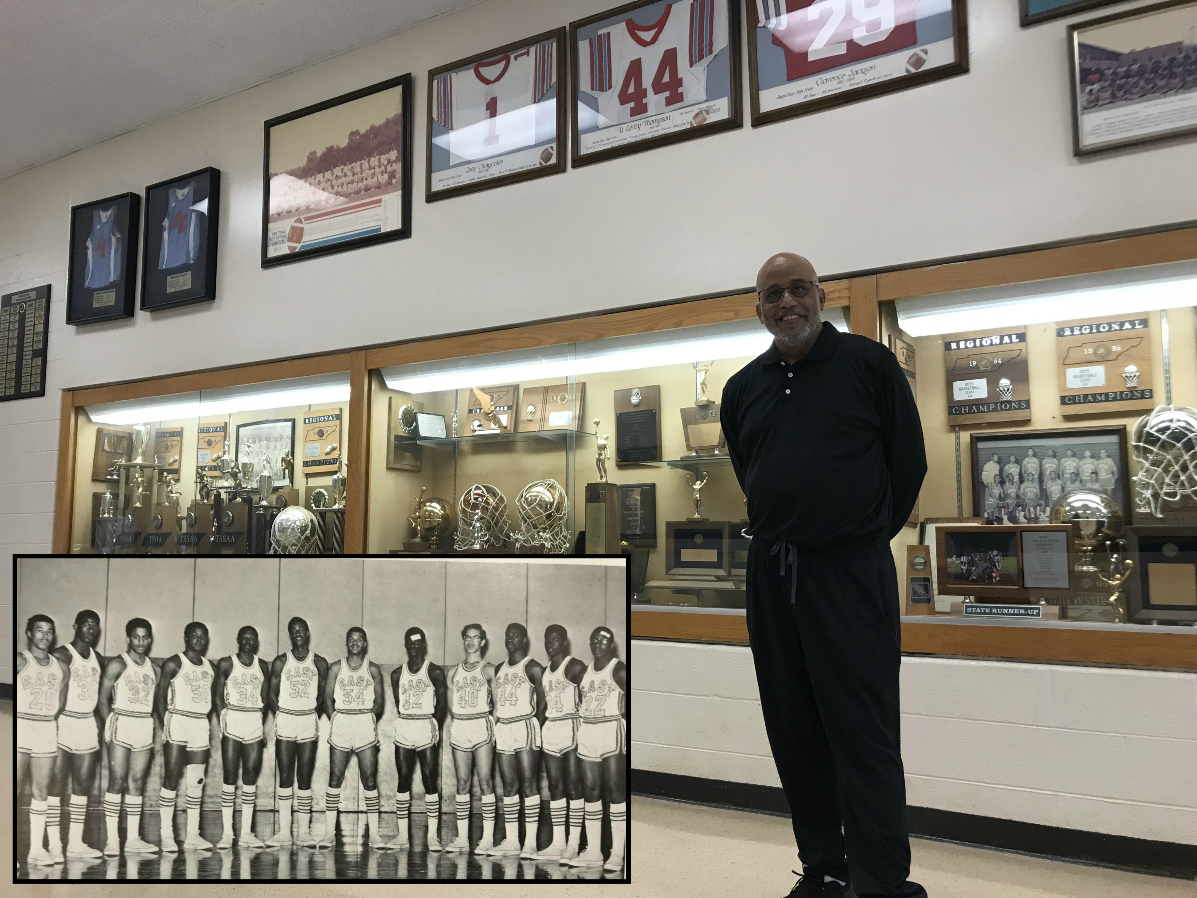 Brian Harvey stands in front of the trophy case at Austin-East High School, his alma mater, on Sep. 17, 2018. At upper left is a yearbook photo, with Harvey third from the left, wearing #32.