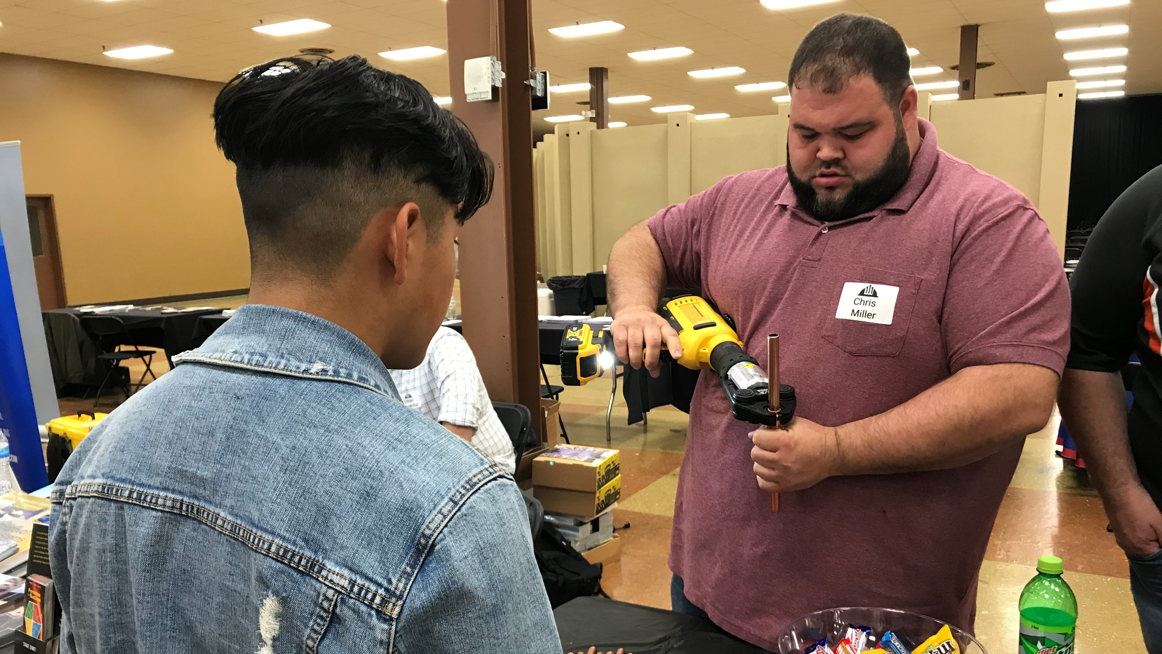 Chris Miller, of HVAC contractor United Services, Inc., demonstrates equipment used by the company during the CTEP career fair.
