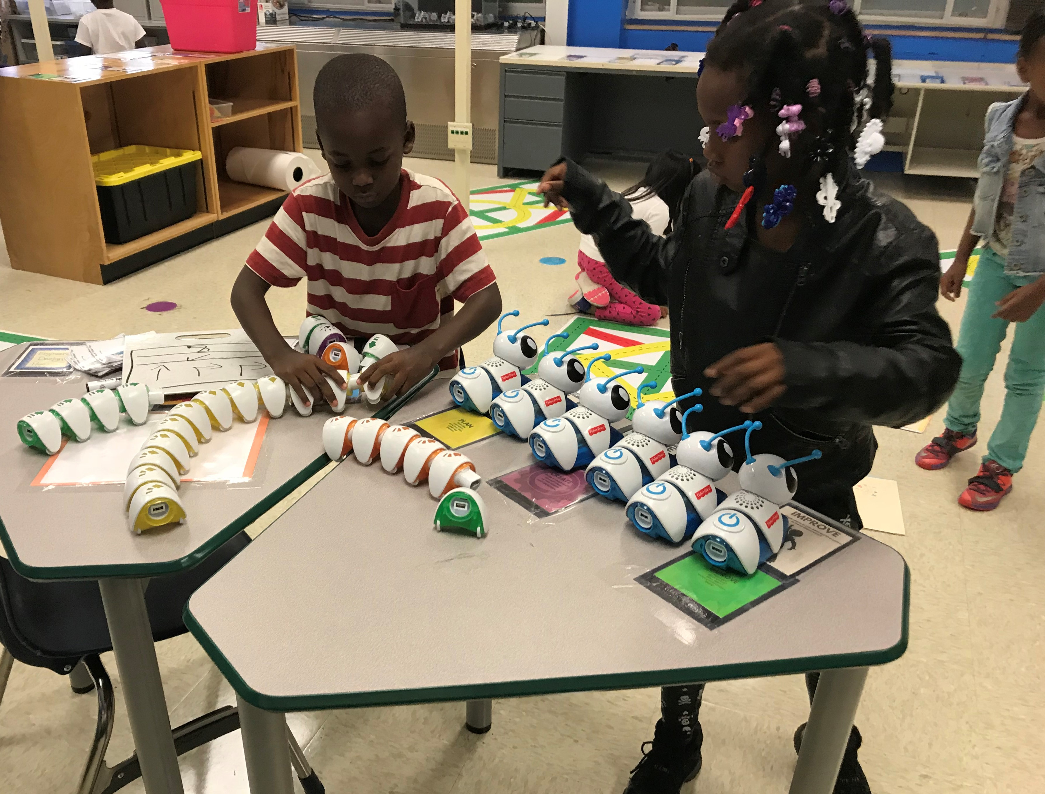 Students in Katie Barnhart's Coding and Robotics lab, at Green Magnet Academy, wrap up a lesson using 'Code-a-Pillars,' segmented robots that provide instruction in writing code and algorithms.