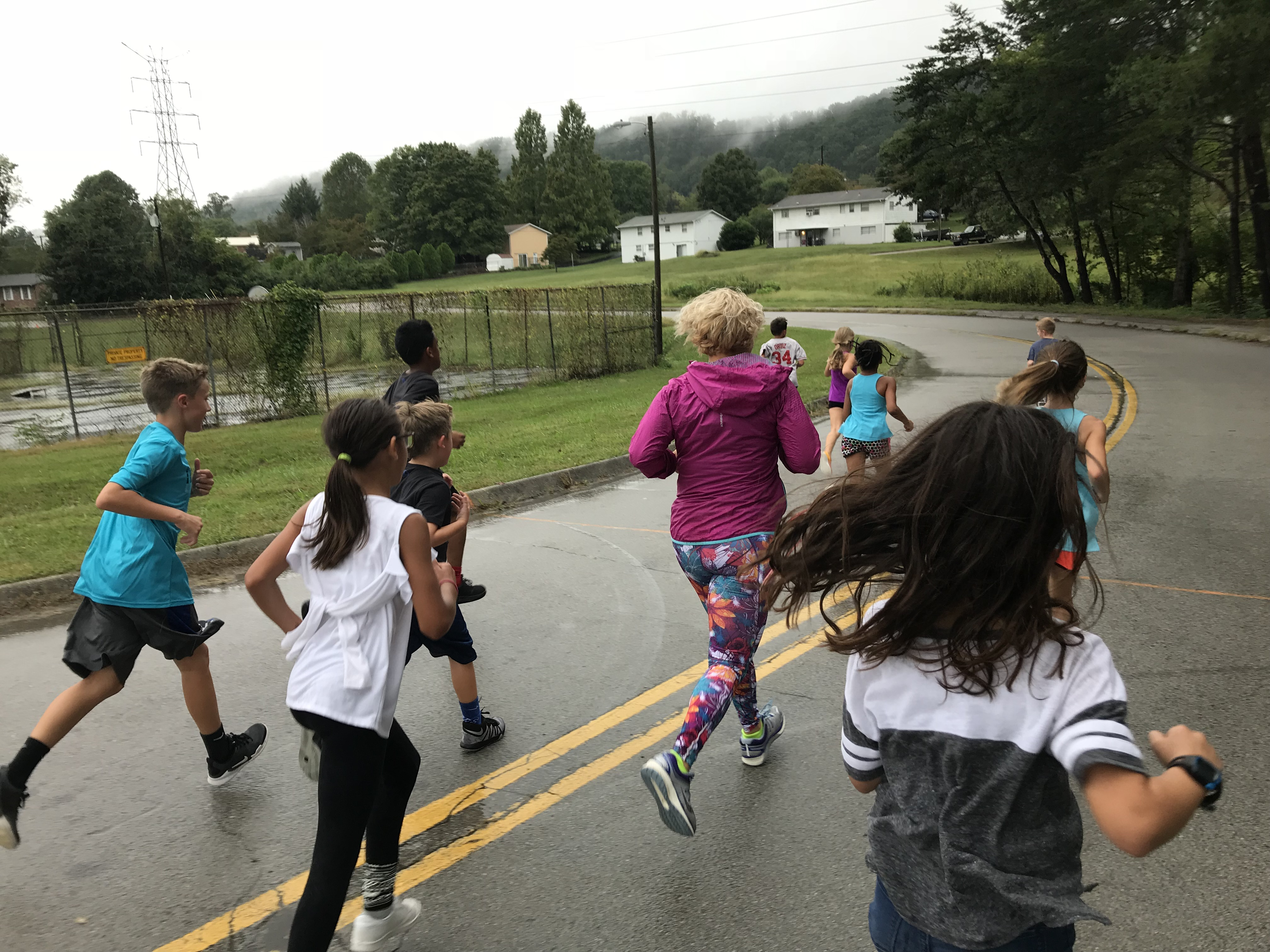 Muna Rodriguez, a parent and assistant coach for the Adrian Burnett Elementary cross-country team, runs with the team on Sept. 26, 2018.