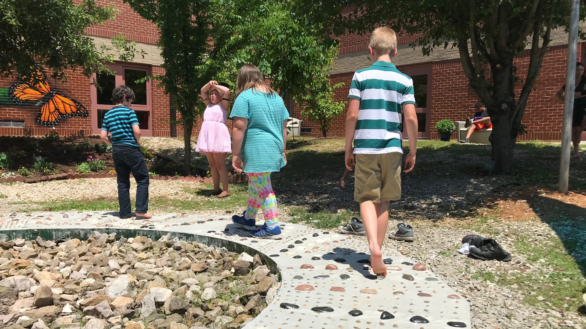 Students navigate a footpath during a ribbon-cutting for Dogwood Elementary's new Outdoor Sensory Courtyard.