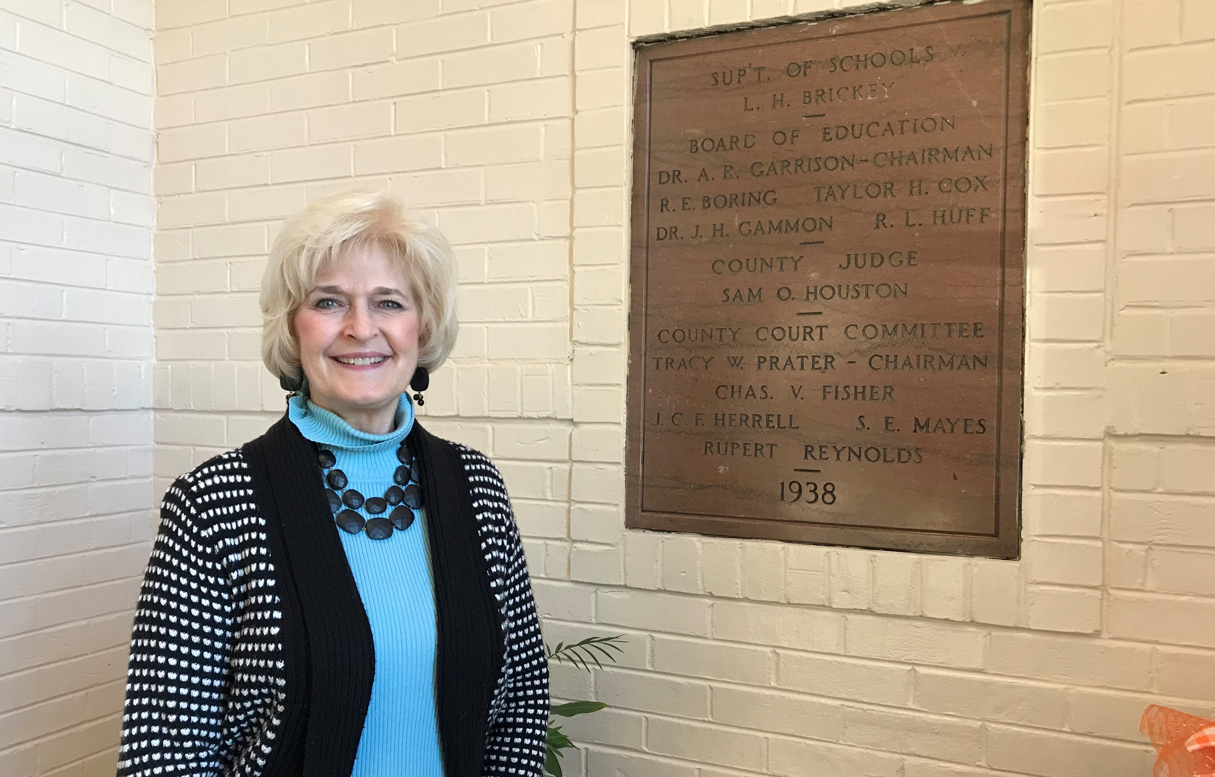Susan Dunlap, Principal of Bearden Elementary School, stands next to a sign commemorating the school's opening in 1938.