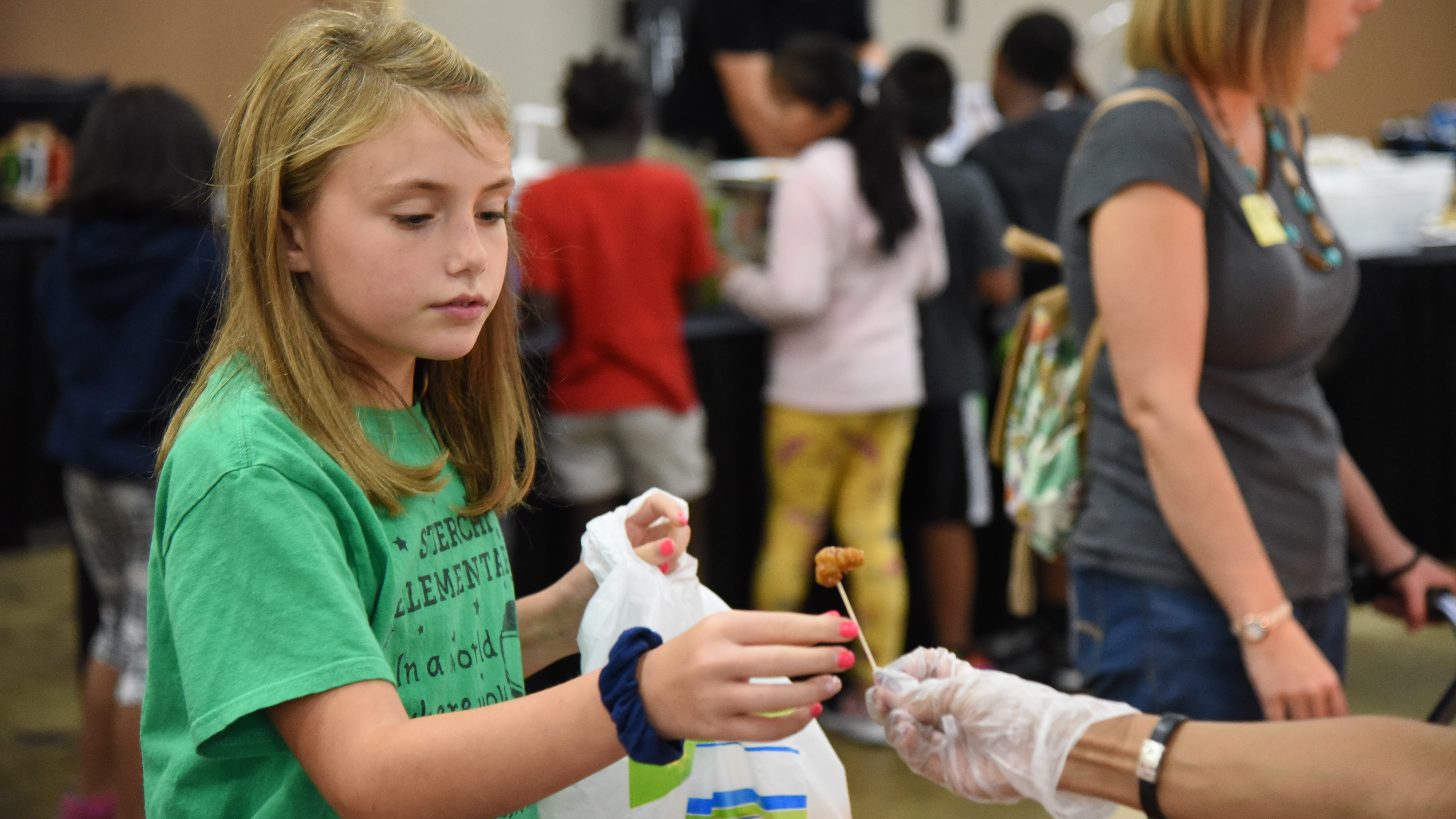 Pyper Clevinger, a 4th-grader at Sterchi Elementary, samples a bite of Tangerine Chicken at the KCS Food Show on Sept. 12, 2019.