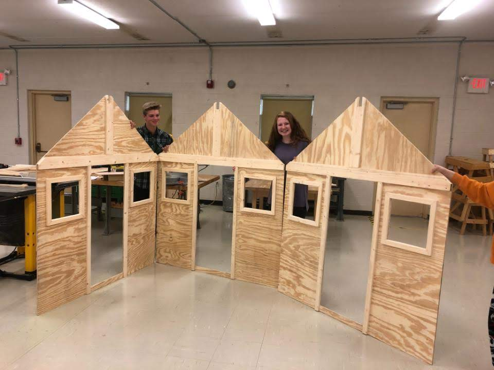 Gibbs High School students Logan Holland and Hadley Parker pose with components of a playhouse their class is building in connection with Habitat For Humanity.