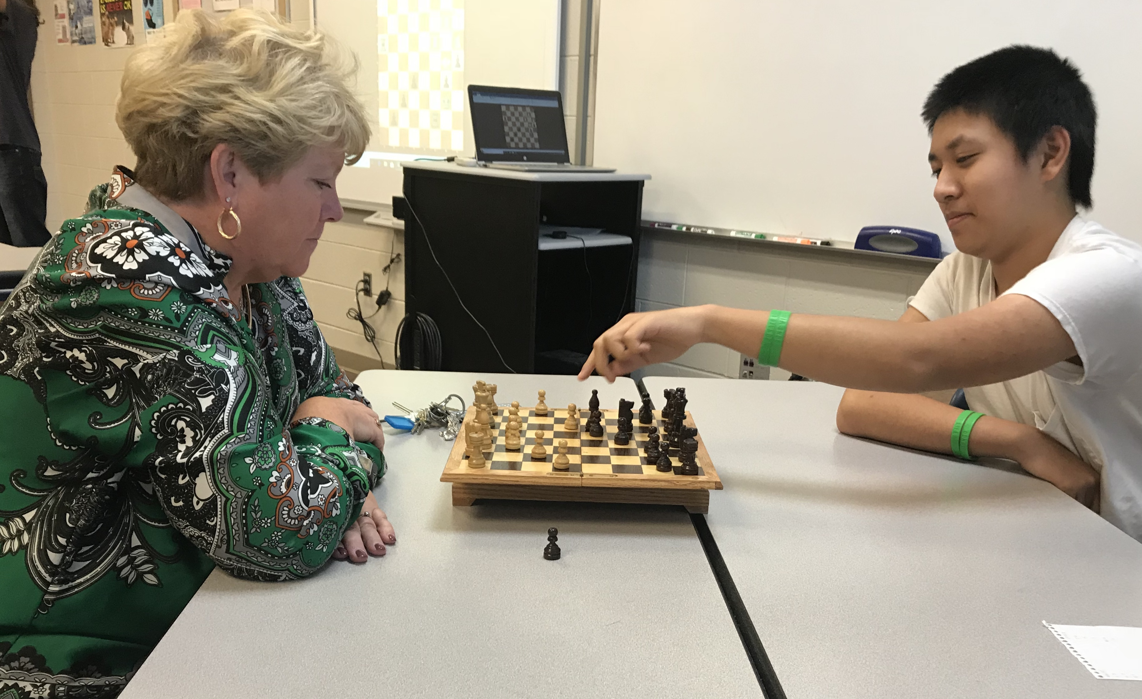 Hardin Valley Academy Principal Sallee Reynolds faces off against HVA sophomore Eric Zhao, during a match at the school's Chess Club meeting.