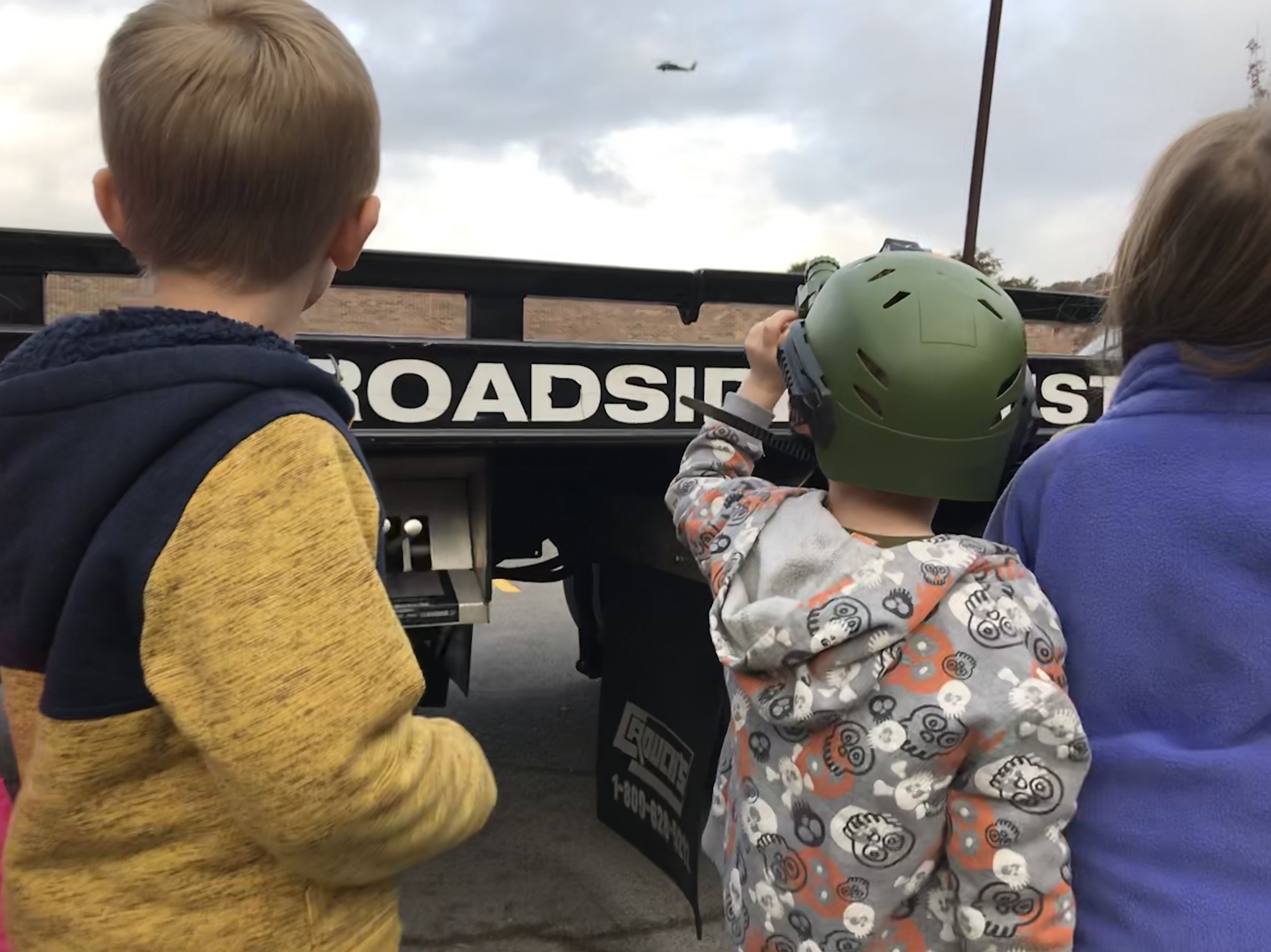 A student at East Knox County Elementary School uses a toy scope to watch as a National Guard helicopter lands at the school for Career Day.