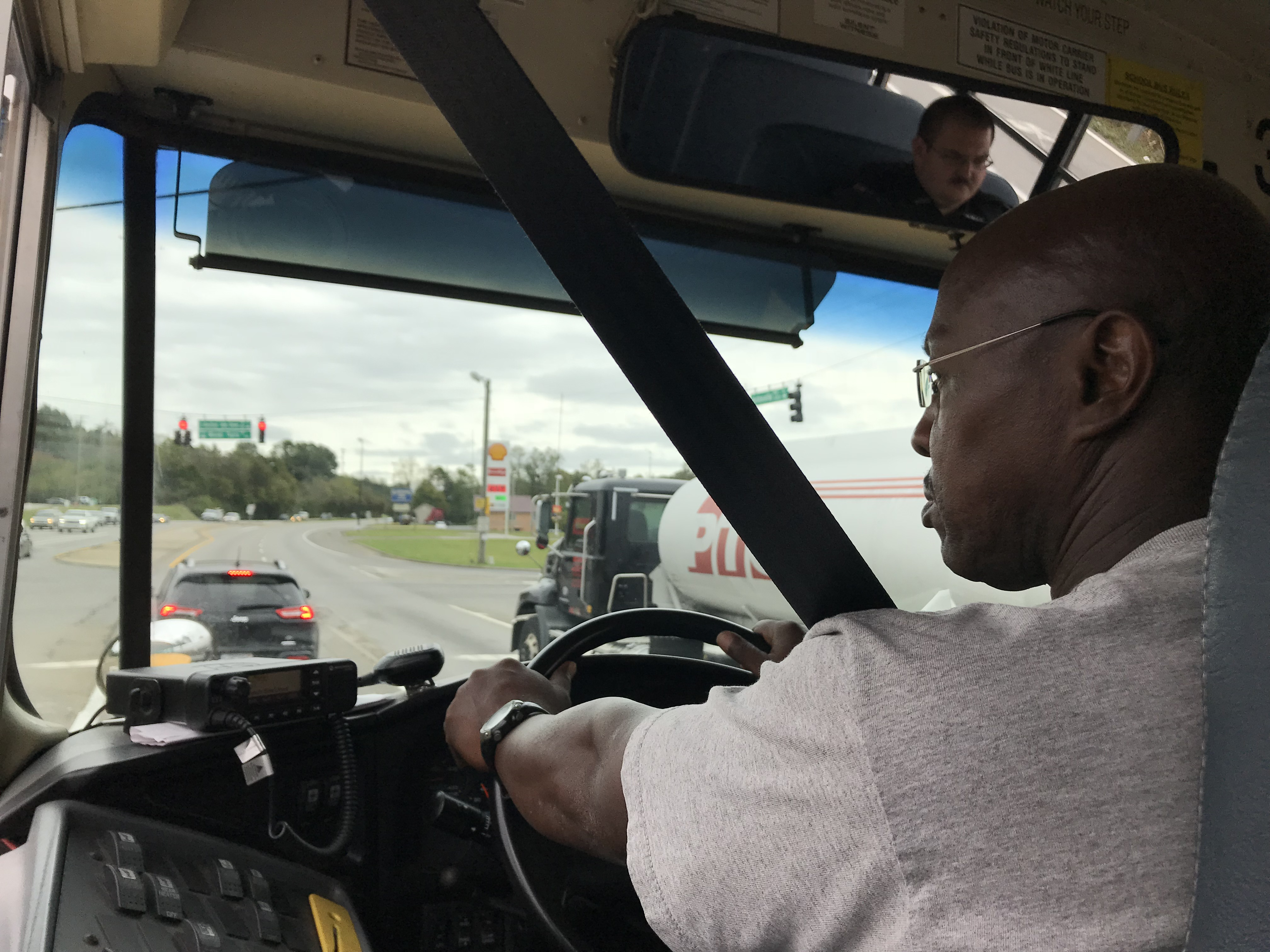 Lynch Bus Lines driver Terry Holloway sits in the driver's seat during a check ride on October 16, 2018. Benjamin Honaker, of the Knox County Schools Security Division, is pictured in the rearview mirror.