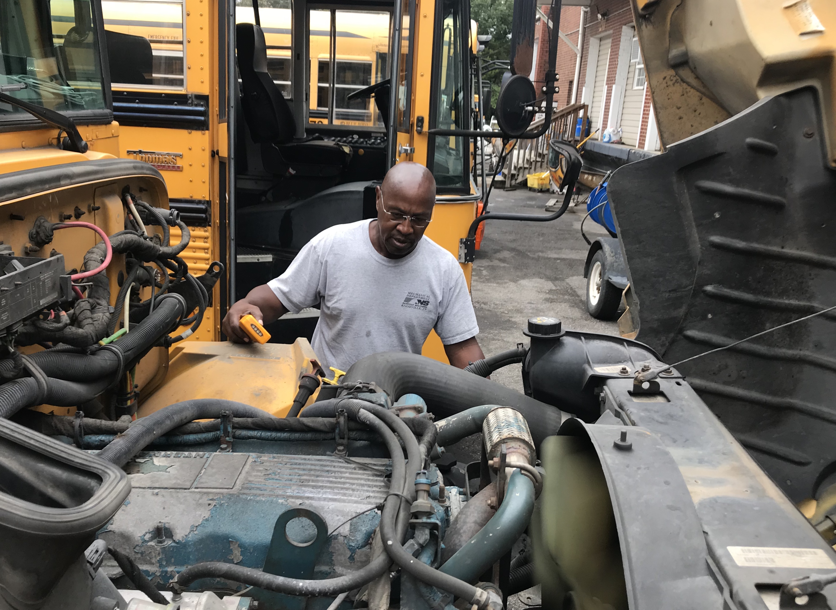 Lynch Bus Lines driver Terry Holloway checks under the hood as part of a standard pre-ride inspection of his school bus.