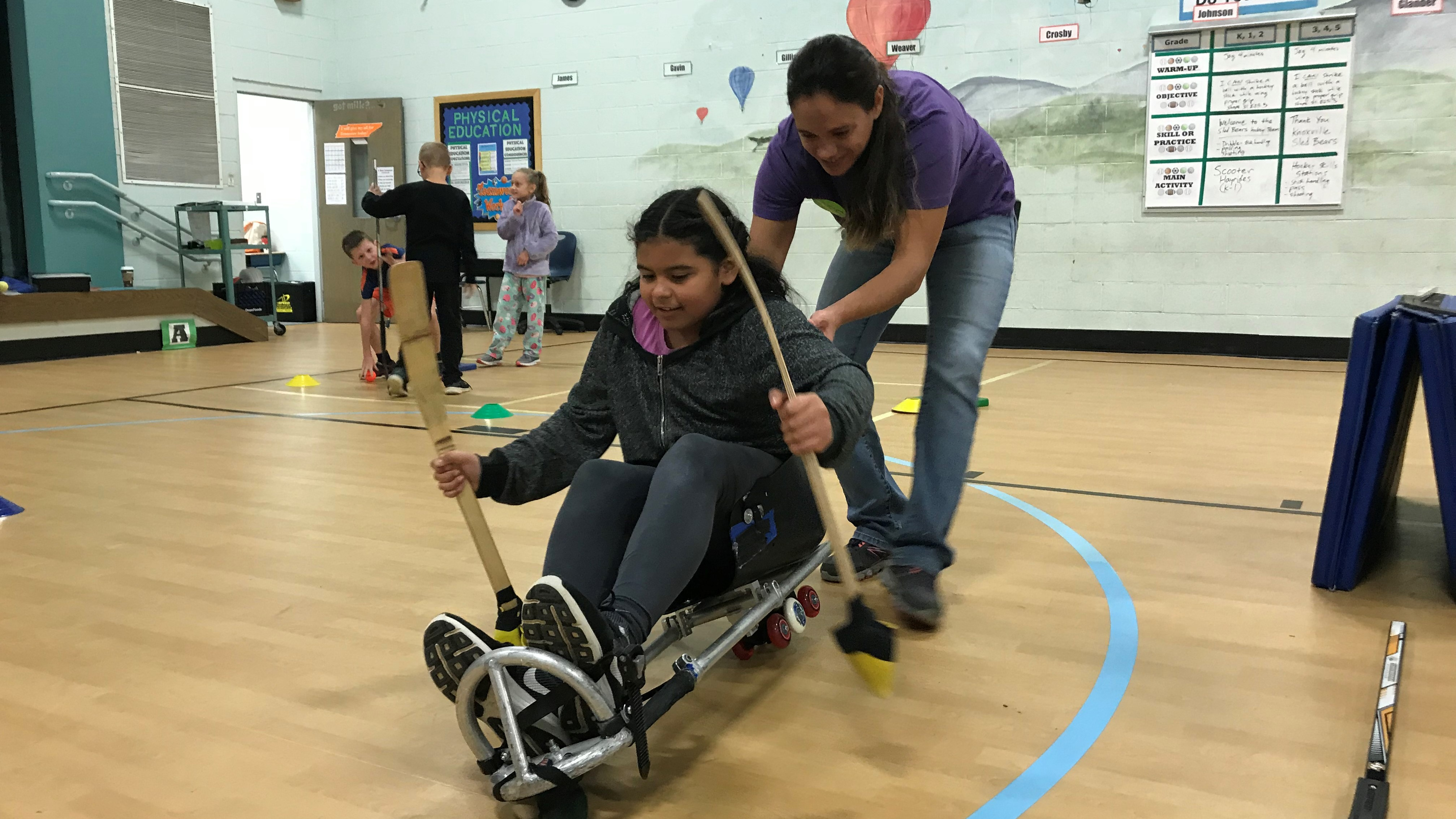Kristin LeBlanc, director of the Knoxville Sled Bears, helps a Ritta Elementary student maneuver on a modified hockey sled.