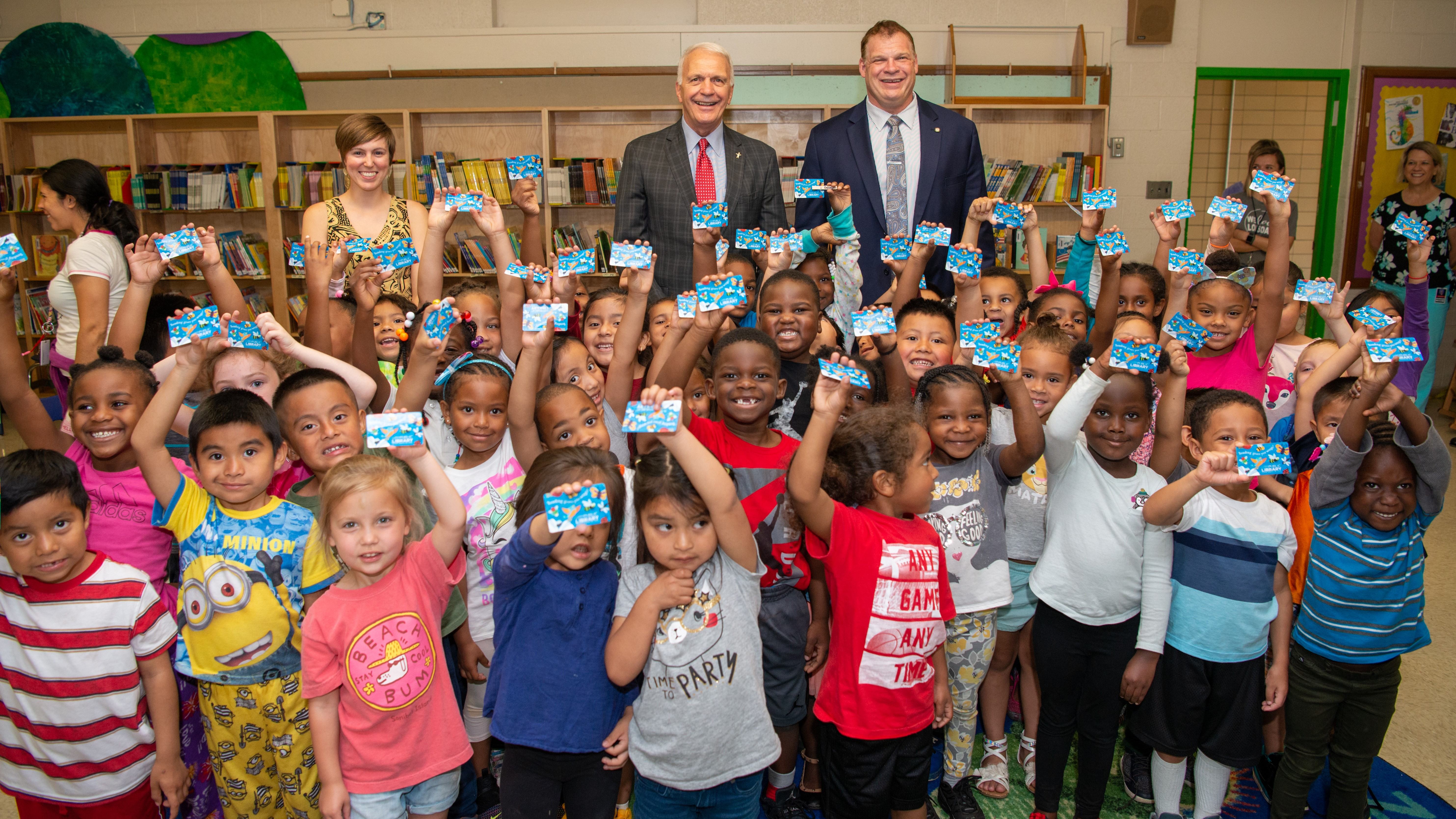 Sam E. Hill Librarian Rachael Nichols, Superintendent Bob Thomas and County Mayor Glenn Jacobs celebrate with students who received library cards..