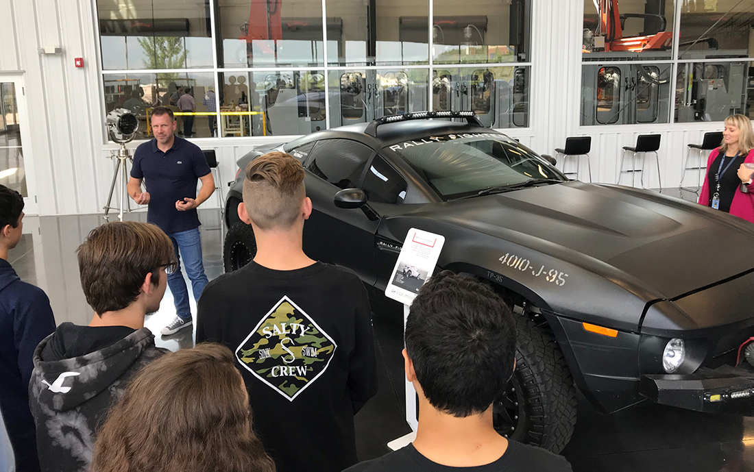 Students from Hardin Valley Academy look on as Gregory Haye, general manager of the Local Motors Knoxville micro-factory, talks about the company's Rally Fighter off-road vehicle.