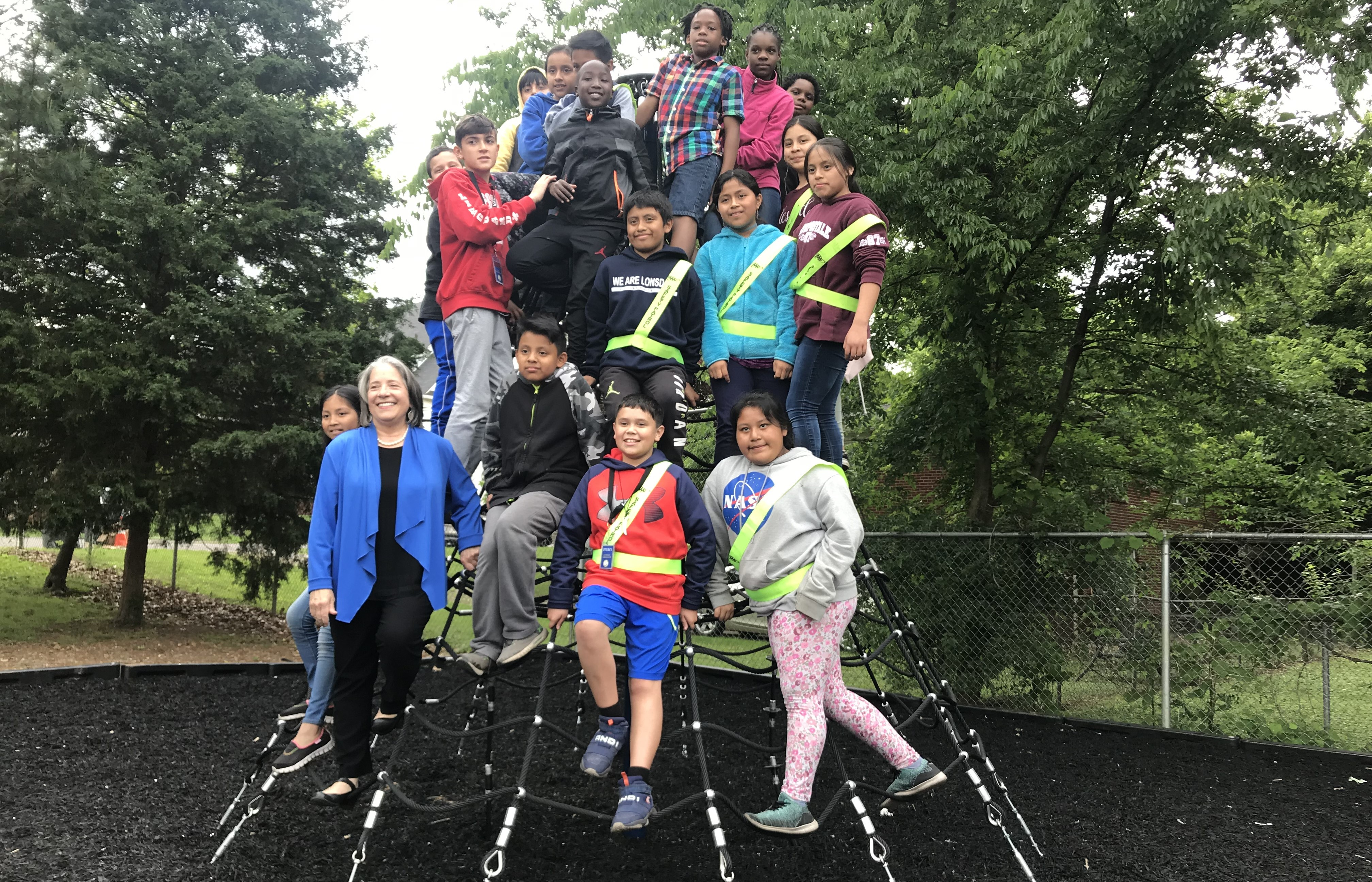 Knoxville Mayor Madeline Rogero poses with Lonsdale Elementary students on a new net climber that was recently installed at the school's playground.