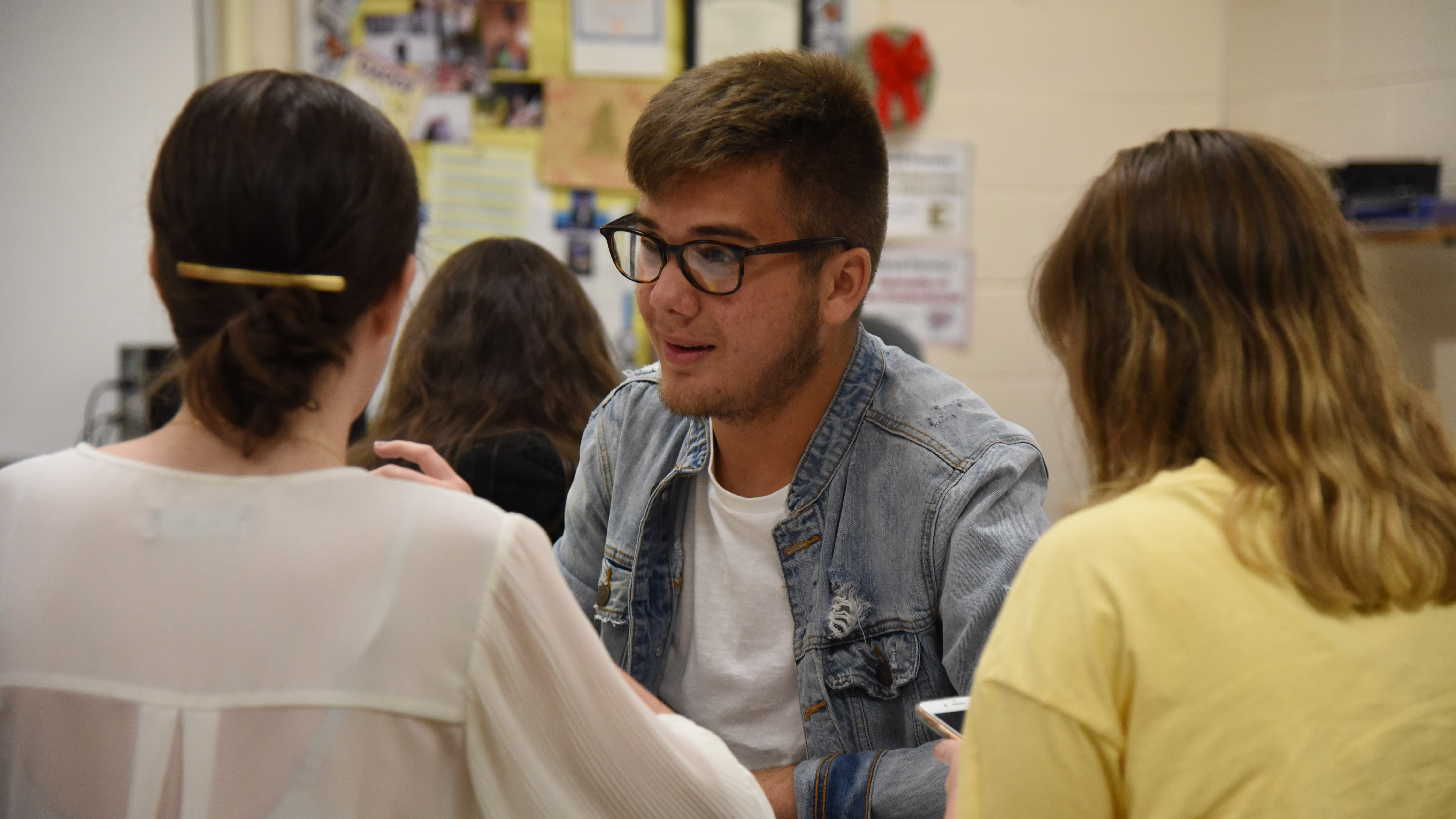 Karns High School senior Noah Kelley, who serves as the Student Representative on the Board of Education, discusses a project with classmates on August 28, 2019.