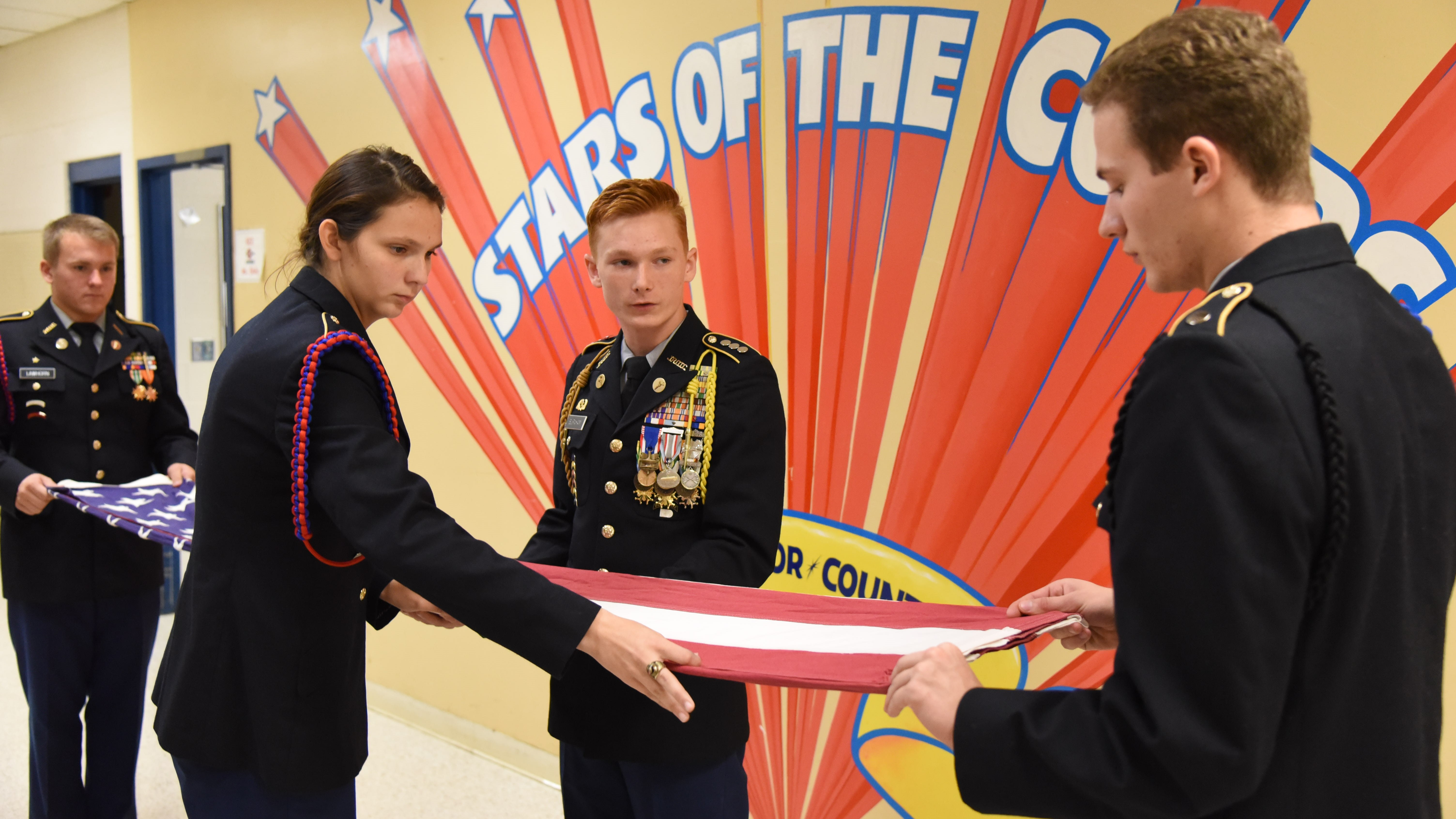Cadets from South-Doyle High School's JROTC Cherokee Battalion fold a flag in preparation for a retirement ceremony next year. From left to right are Taylor Lawhorn, Kaitlyn Scalf, Avery Burnham and Justin Shipes.
