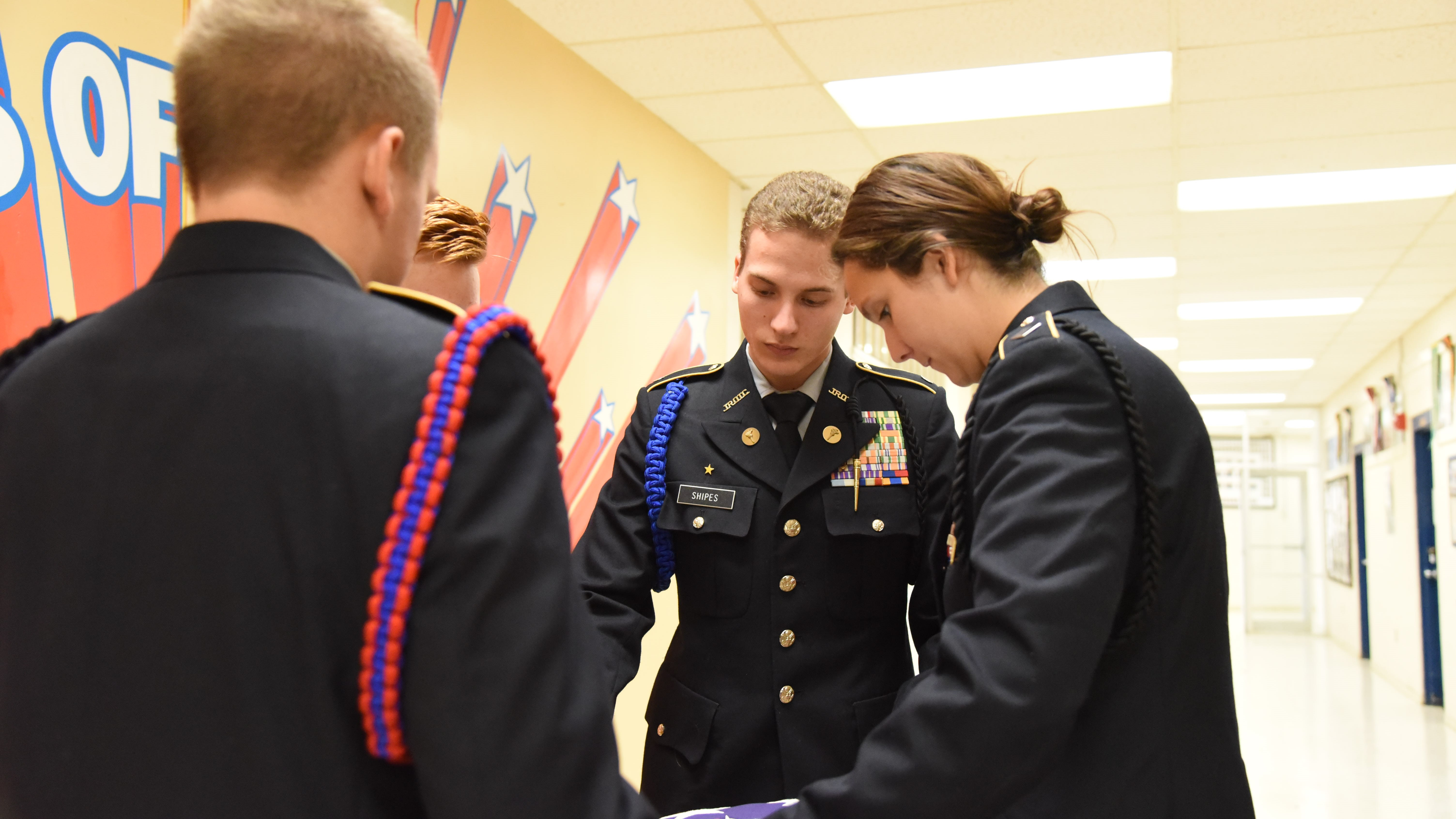 Justin Shipes, center, and other cadets from South-Doyle High School's JROTC fold a flag for retirement. The school's Cherokee Battalion is hoping to retire 1,000 flags next spring.