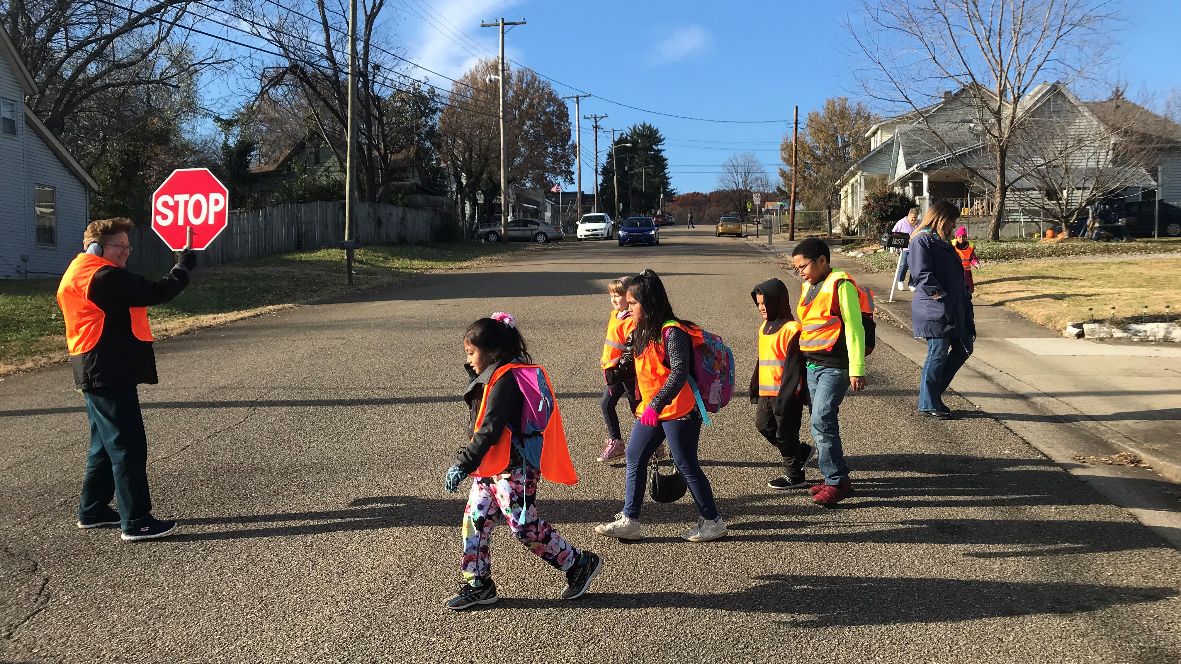 Teaching assistant Cindy Poland holds a stop sign as students from West View Elementary School cross the street.
