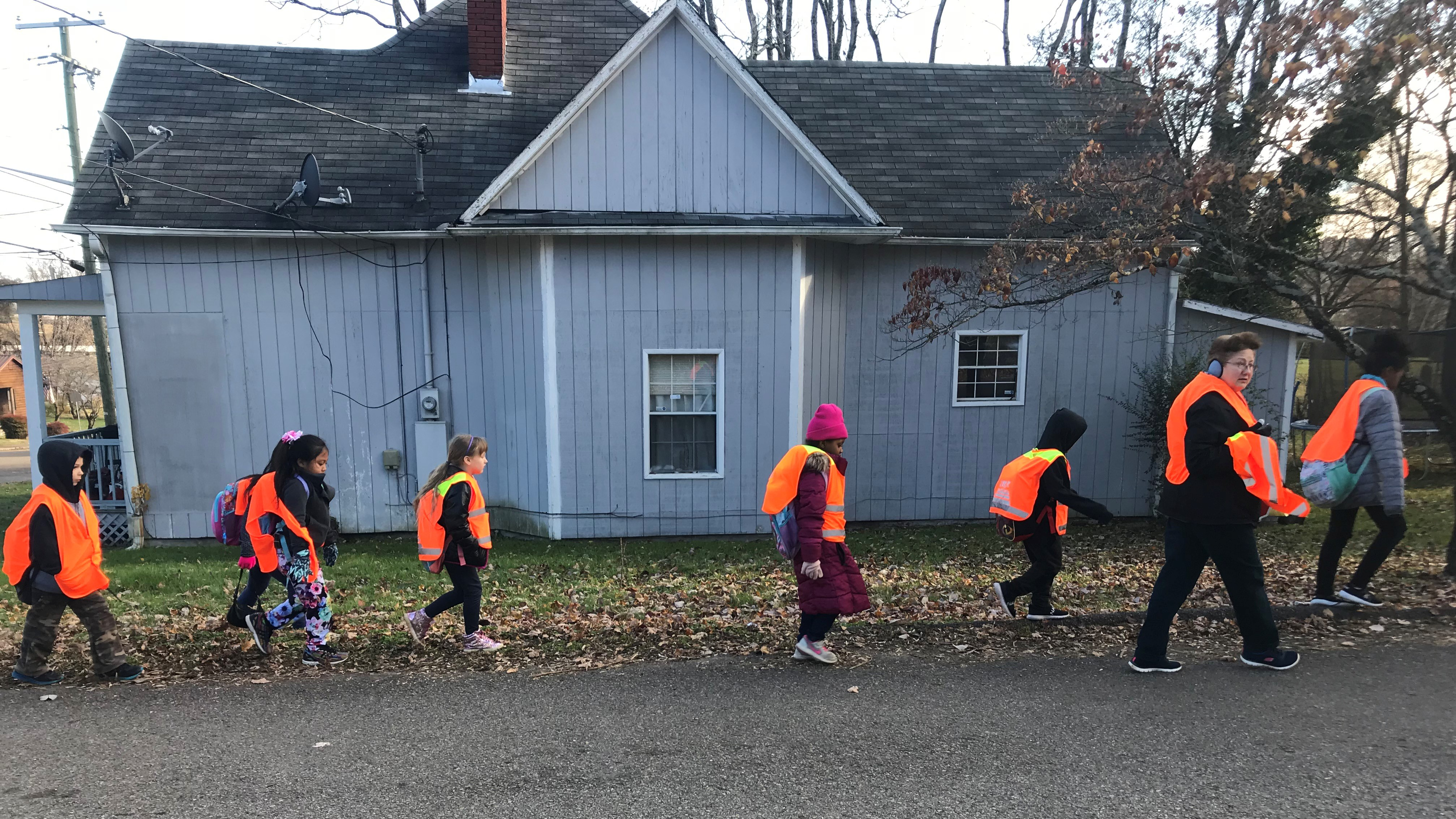 Teaching assistant Cindy Poland leads students from West View Elementary School as they participate in the Walking School Bus program..